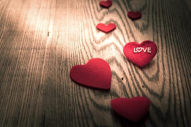 Palavra de amor no coração vermelho sobre os fundos de mesa de madeira com espaço de cópia