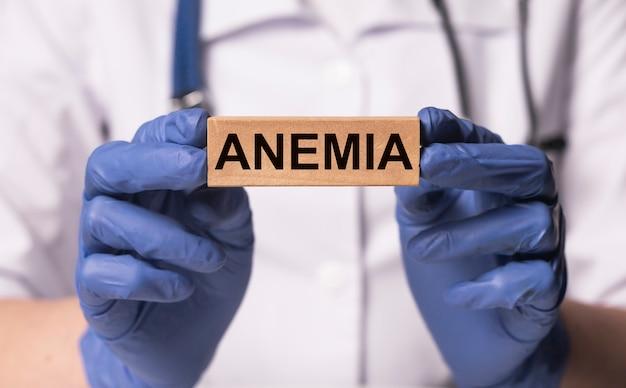 Palavra de anemia em bloco de madeira na mão do médico