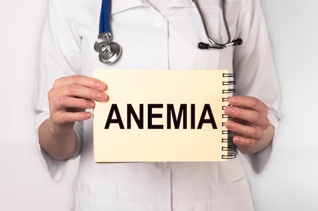 Palavra de anemia no papel na mão do médico