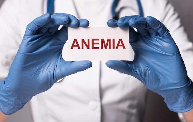 Palavra de anemia no papel no médico com as mãos nas luvas close-up