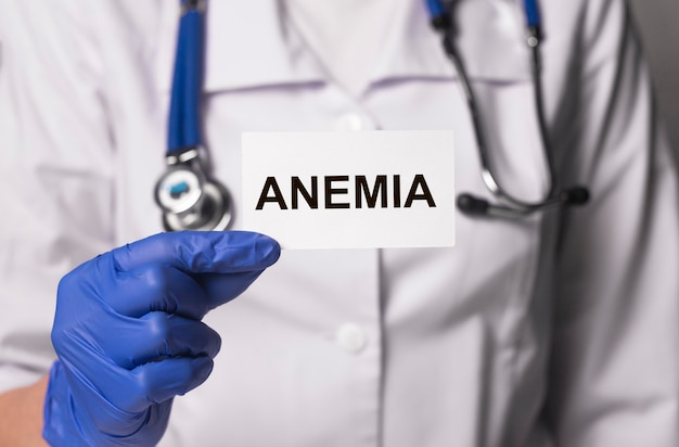 Palavra de anemia no papel no médico com as mãos nas luvas