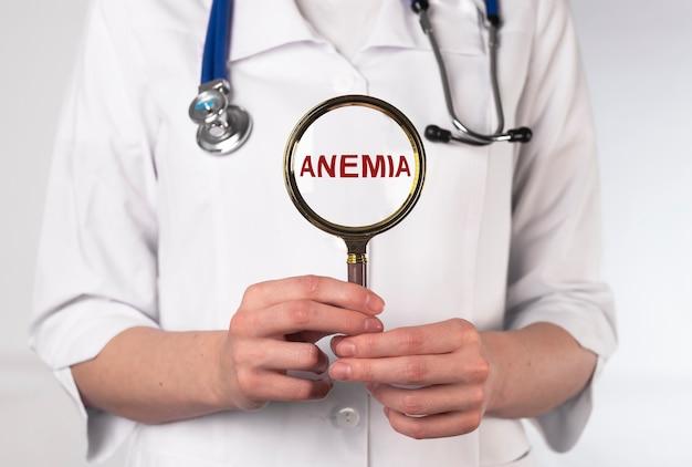 Palavra de anemia por meio de lupa na mão do médico