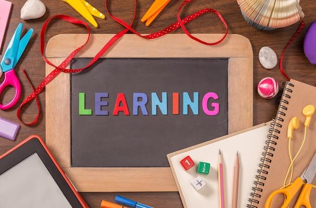 Palavra de aprendizagem formada por alfabetos de cor de madeira na pequena lousa com material escolar