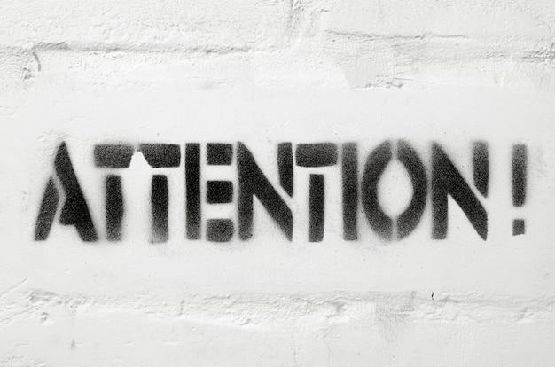 Palavra de atenção impressa com estêncil texturizado na parede de tijolos brancos