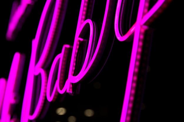 Palavra de bebê em próton roxo neon cor em fundo preto conceito moderno dos anos 80