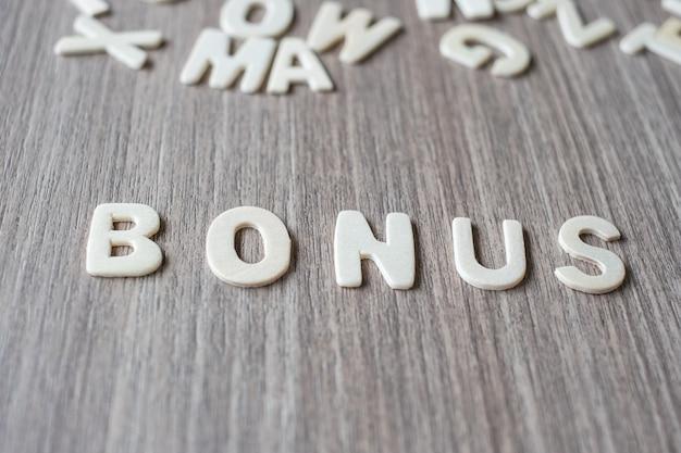 Palavra de bônus de letras do alfabeto de madeira. conceito de negócio e idéia