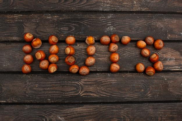 Palavra de castanhas maduras nozes em forma de uma mesa de madeira marrom