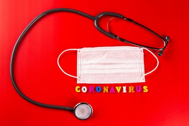 Palavra de coronavírus feita de letras coloridas na superfície vermelha. a inscrição no coronavírus de máscara protetora médica.