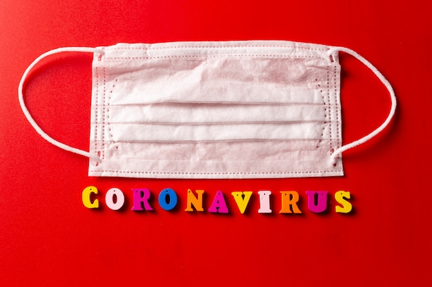 Palavra de coronavírus feita de letras coloridas sobre fundo vermelho. a inscrição no coronavírus de máscara protetora médica.