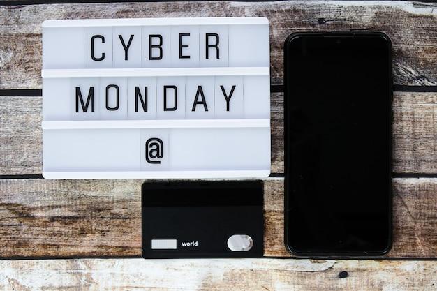 Palavra de cyber segunda-feira escrita na mesa de luz em madeira marrom. camada plana, vista superior.