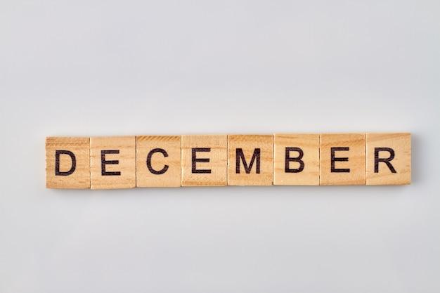 Palavra de dezembro escrita em blocos de madeira. isolado no fundo branco.