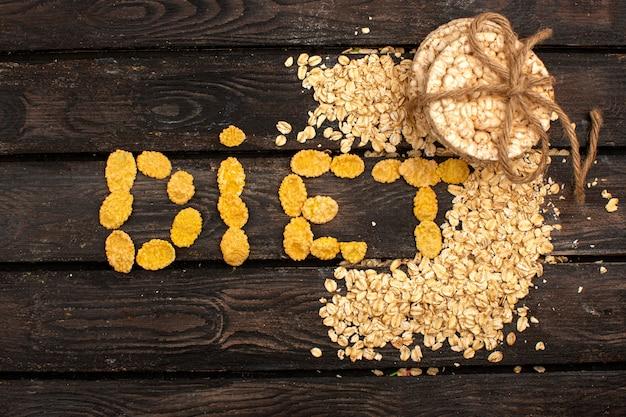 Palavra de dieta saborosa picante salgada de batatas fritas e cereais em forma de juntamente com biscoitos de pão amarrado no chão rústico de madeira marrom
