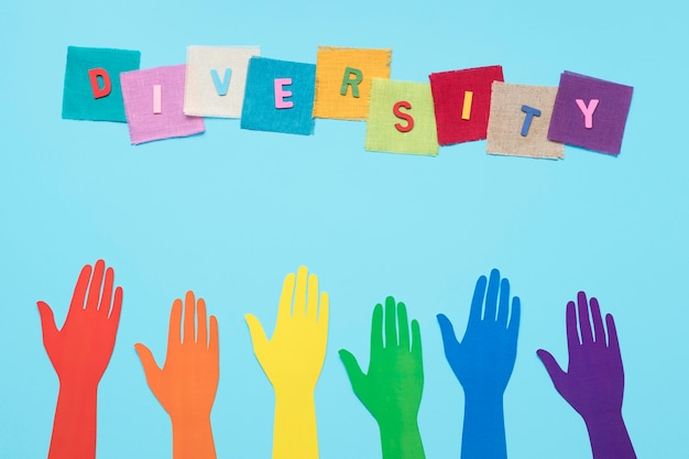 Palavra de diversidade feita com cartões coloridos ao lado de ponteiros de papel colorido