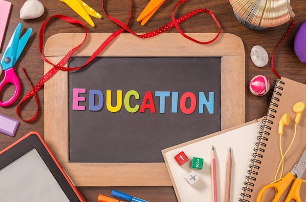 Palavra de educação formada por alfabetos de madeira cor na pequena lousa com material escolar