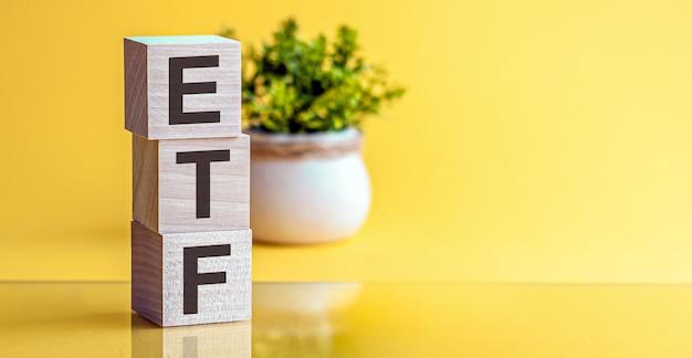 Palavra de etf feita de cubos de madeira em um fundo amarelo com espaço de cópia, conceito de negócio