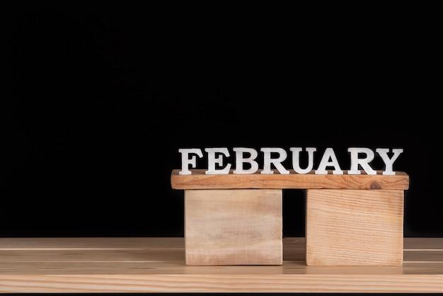 Palavra de fevereiro de letras de madeira. calendário de madeira. fundo preto. espaço para texto.