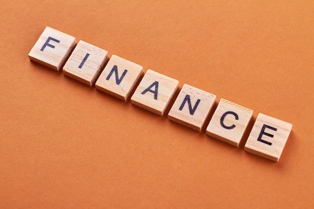 Palavra de finanças em cubos de madeira. conceito de investimento e economia de dinheiro. blocos de madeira com letras isoladas em fundo laranja.