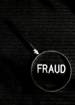 Palavra de fraude com letra em uma lupa plana leigos