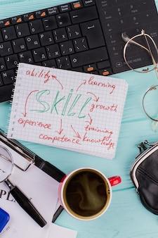 Palavra de habilidade de close-up no bloco de notas com teclado de café. carteira de óculos com caneta preta.