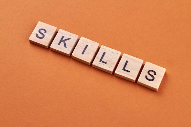 Palavra de habilidades escrita em blocos de madeira. texto de habilidades em cubos de madeira isolados em fundo laranja.