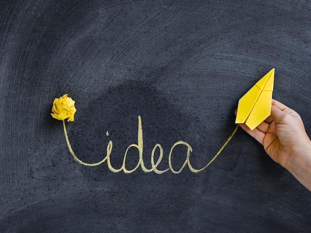 Palavra de idéia escrita no quadro-negro e avião de papel