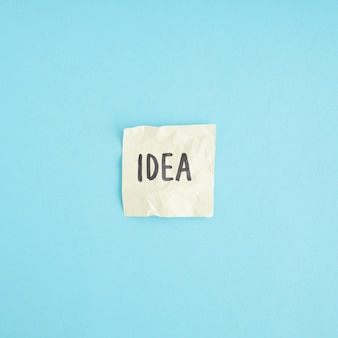 Palavra de idéia no papel amassado contra o fundo azul