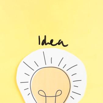 Palavra de idéia sobre lâmpada de recorte de papel no pano de fundo amarelo