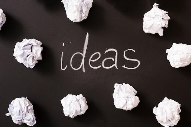 Palavra de idéias cercada com bolas de papel amassado branco na lousa