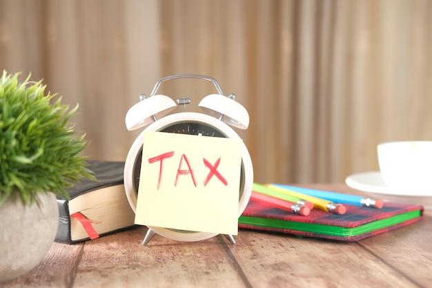 Palavra de imposto no despertador com estacionário na mesa.