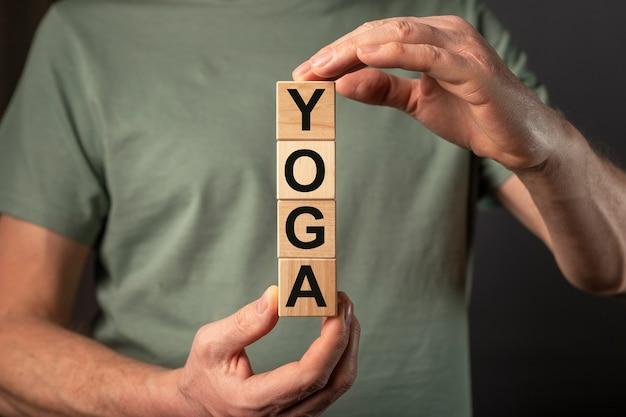 Palavra de ioga em cubos de madeira em mãos masculinas.