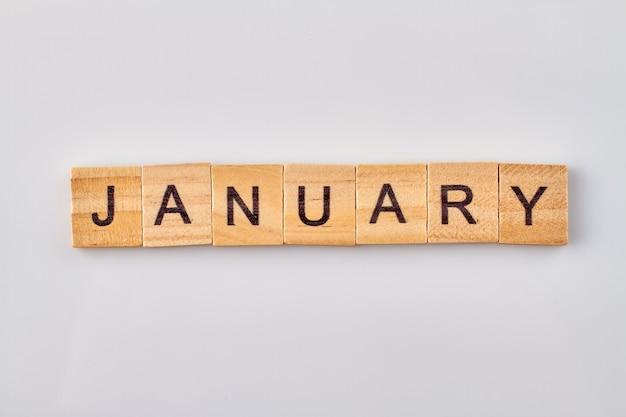 Palavra de janeiro escrita em blocos de madeira. isolado no fundo branco.