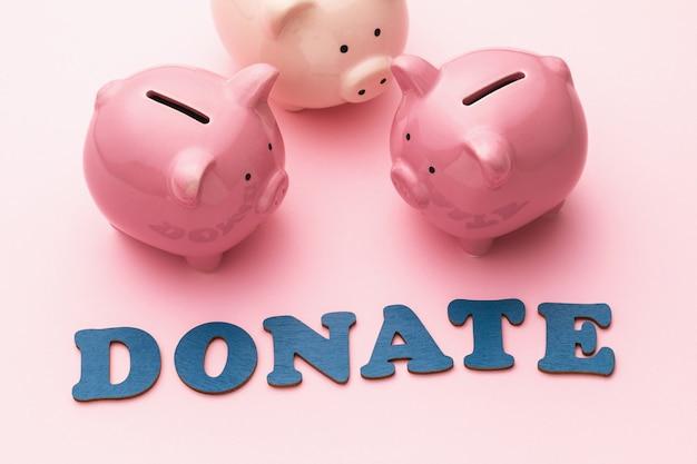 Palavra de letras de madeira e três cofrinhos em um fundo rosa, conceito sobre o tema da doação de dinheiro