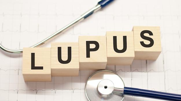 Palavra de lúpus escrita em blocos de madeira e estetoscópio sobre fundo claro. conceitos de saúde para hospitais, clínicas e negócios médicos.