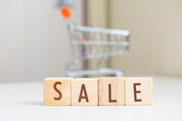Palavra de madeira da venda do bloco do cubo na tabela com mini carrinho de compras.