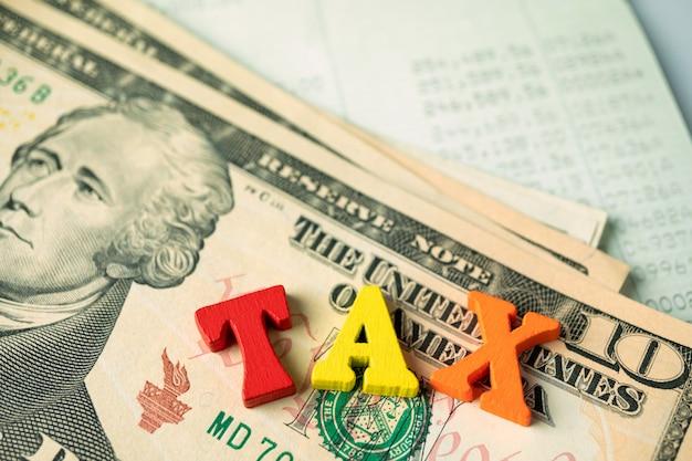 Palavra de madeira do imposto na nota de banco e moeda dourada e banco do livro.