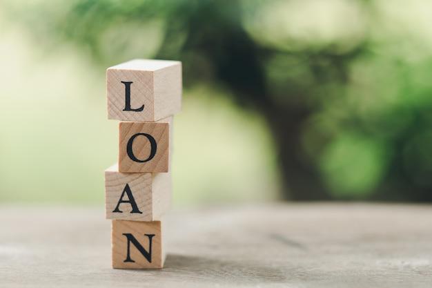 Palavra de madeira empréstimo em pé na mesa de madeira, usando como conceito de negócio de fundo