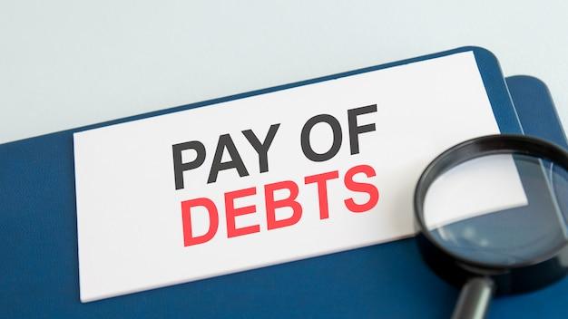 Palavra de pagamento de dívidas em cartão de papel branco e lente de aumento