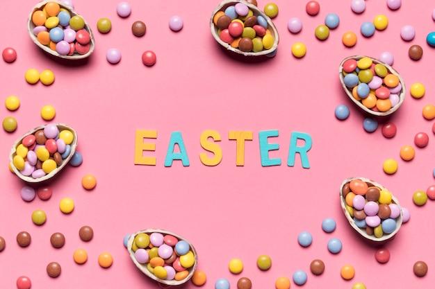 Palavra de páscoa cercada com doces coloridos de gema e ovos de páscoa no fundo rosa