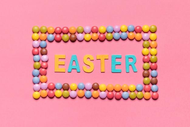 Palavra de páscoa dentro do quadro de doces coloridos gem sobre o pano de fundo-de-rosa