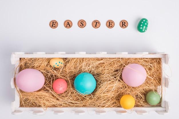 Palavra de páscoa perto de ovos entre feno na caixa