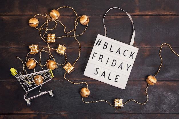 Palavra de promoção de sexta-feira negra na mesa de luz e pequeno carrinho de compras com presentes