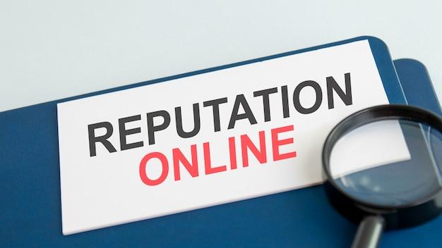 Palavra de reputação online em cartão de papel branco e lente de aumento