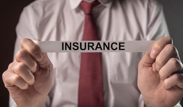 Palavra de seguro no papel nas mãos do agente de camisa e gravata