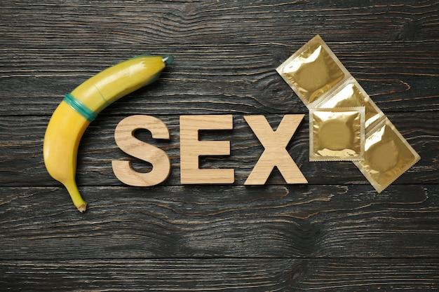 Palavra de sexo, banana e preservativos na superfície de madeira