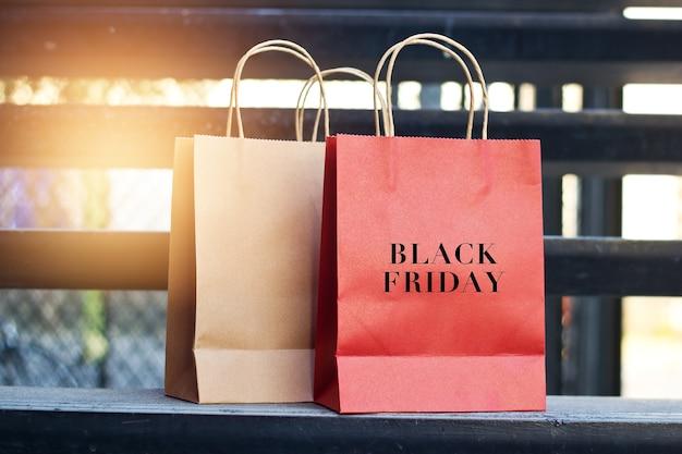 Palavra de sexta-feira negra em sacos de compras de papel vermelho e marrom colocados nas escadas ao ar livre