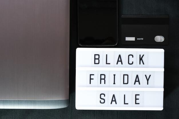 Palavra de sexta-feira negra escrita na mesa de luz em têxteis pretos. camada plana, vista superior
