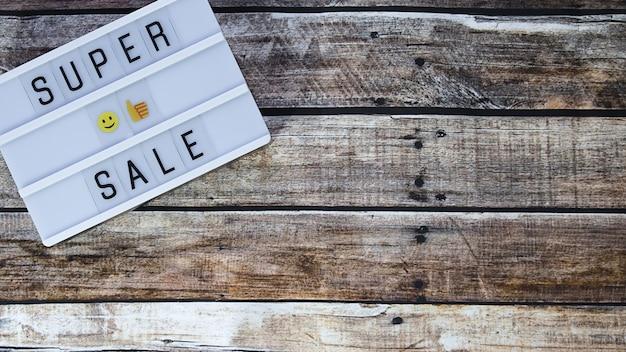 Palavra de super venda escrita na mesa de luz em madeira marrom. camada plana, vista superior.