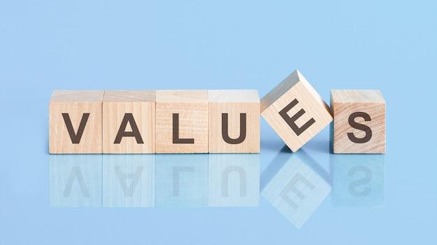Palavra de valores escrita em blocos de madeira na mesa azul, conceito de negócio