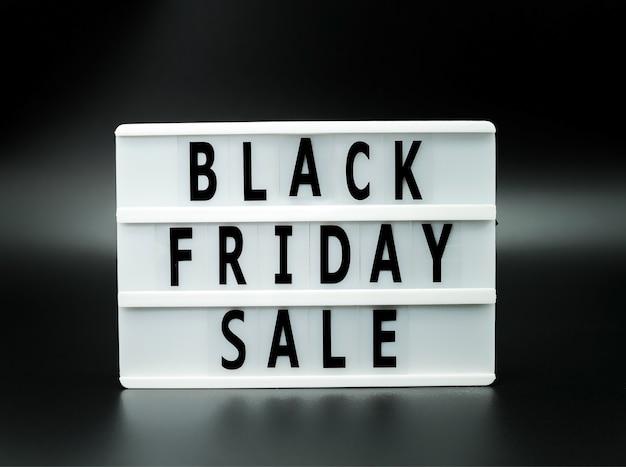 Palavra de venda de sexta-feira negra na mesa de luz em fundo preto