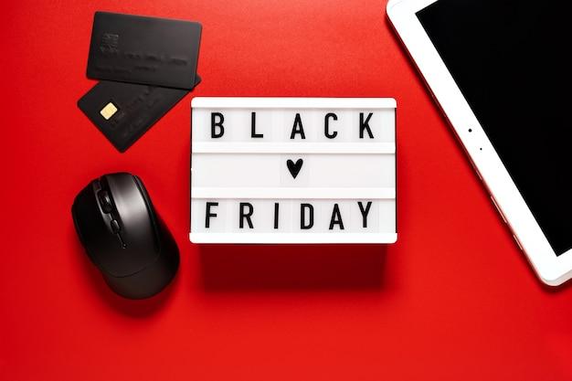 Palavra de venda de sexta-feira negra na mesa de luz em um fundo vermelho.